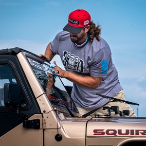 Man applying decal to upper part of windshield