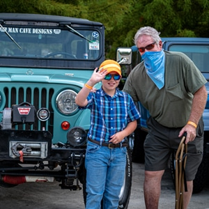 Man and boy in front of blue Jeep