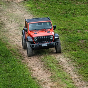 Orange Jeep running through an all terrain course