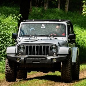 Silver Jeep driving through wooded trail