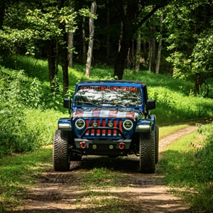 Red, white, and blue Jeep on the trail