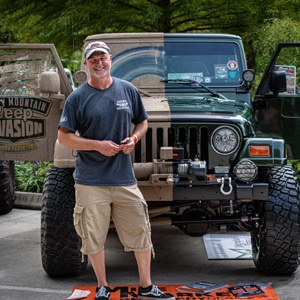 Man standing in front of Jeep that is half covered in mud