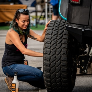 Woman checking a tire on her Jeep