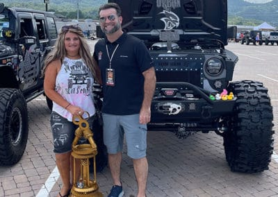 2021 award winner woman with black Jeep standing with man who presented award