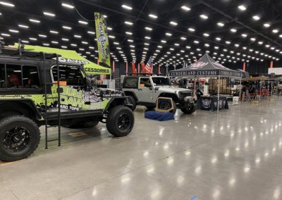 Main showroom area filled with vendors and Jeeps