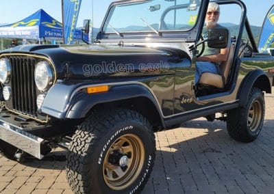 Man with open top black Jeep on display